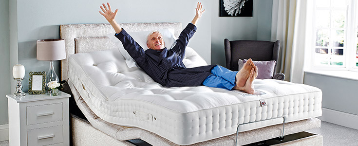 An elderly man laying on a Comfomatic bed