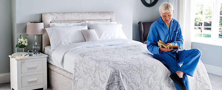 An elderly man reading on a Comfomatic bed