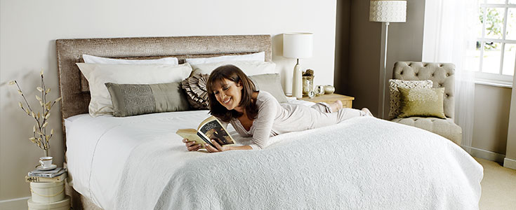 A lady laying on top of a Comfomatic bed