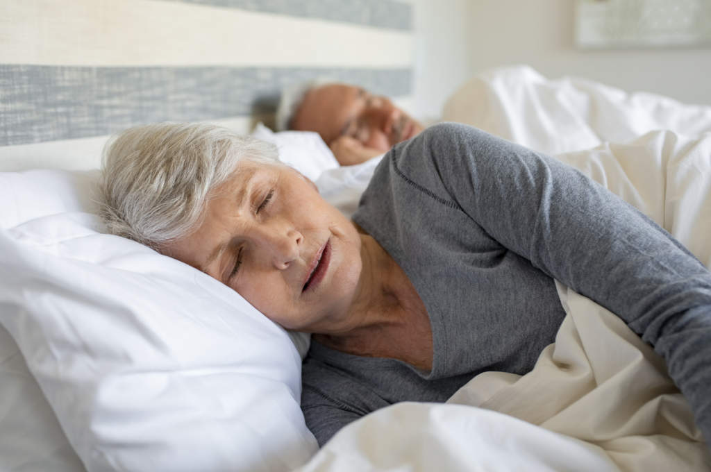 An elderly woman asleep in bed with her partner